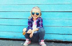 Stylish child with sweet lollipop in city over colorful blue Royalty Free Stock Photos