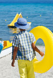 Stylish child wearing colorful clothes and holding yellow float at beach Royalty Free Stock Photos