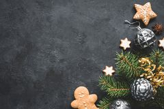 Stylish Christmas background with vintage toys, fir tree and cookies on black stone background. stock photos