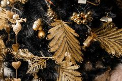 Christmas decorative garland in golden tones and in a form of leafs, angels and cones. Stylish Christmas decorative garland in golden tones and in a form of stock photography