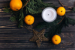 Stylish christmas flat lay with green branches and oranges and g. Olden star on black rustic wooden background. seasonal greeting and shopping advertising Royalty Free Stock Photo