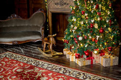Stylish Christmas interior decorated in red and golden colors Stock Photos