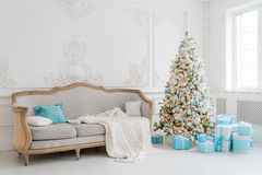 Stylish Christmas interior with an elegant sofa. Comfort home. Presents gifts underneath the tree in living room Stock Photography