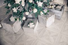 Stylish Christmas interior with white and silver ornaments. Comfort home. Presents gifts and christmas tree.Presents royalty free stock photography