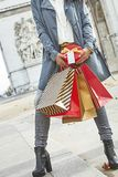 Happy young woman shopper near Arc de Triomphe in Paris, France. Stylish Christmas in Paris. Closeup on happy young woman in sunglasses with shopping bags and Stock Image