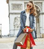 Happy young woman shopper near Arc de Triomphe in Paris, France. Stylish Christmas in Paris. Full length portrait of happy young woman in sunglasses with Stock Image
