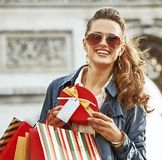 Happy woman with Christmas present near Arc de Triomphe in Paris. Stylish Christmas in Paris. Portrait of happy elegant woman in trench coat with shopping bags Royalty Free Stock Image