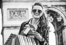 Woman with Christmas present near Arc de Triomphe in Paris. Stylish Christmas in Paris. Portrait of happy elegant woman in trench coat with shopping bags and Royalty Free Stock Photography