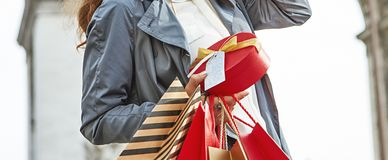 Elegant woman shopper near Arc de Triomphe. Stylish Christmas in Paris. smiling elegant woman in trench coat with shopping bags and Christmas present near Arc de Royalty Free Stock Photo
