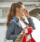 Woman shopper near Arc de Triomphe looking into distance. Stylish Christmas in Paris. smiling modern woman in sunglasses with shopping bags and Christmas present Royalty Free Stock Photo