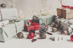 Stylish christmas wrapped presents with ornaments and cones on w. Hite wooden background top view, space for text. merry christmas concept. seasonal greetings Stock Photos