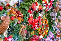 Stylish christmas wreaths with red berries,ornaments, pine cones, branches on in european city street.  stock image