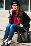 The stylish city girl in sunglasses  sits on steps Royalty Free Stock Photography