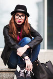 The stylish city girl in sunglasses  sits on steps Royalty Free Stock Image