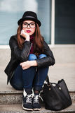 The stylish city girl in sunglasses  sits on steps Stock Photos