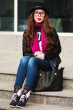 The stylish city girl in sunglasses  sits on steps Stock Photo