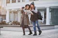 Stylish city portrait of two fashionable girls walking in Europe modern city centre. Fashionable friends travelling with stock image
