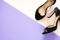 Stylish classic black women`s leather sandals shoes with high heels on pink purple multi-colored paper background. Copy space. Top view. Flat lay. Celebration stock images