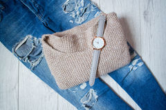Stylish clock on a sweater and torn jeans. Fashionable concept, wooden background, top view Royalty Free Stock Photography