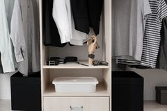 Stylish clothes and accessories in large wardrobe. Closet stock photo