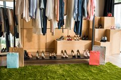 Stylish clothes on hangers and fashionable shoes. In boutique stock photo
