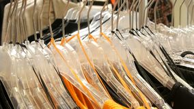 Stylish clothes hanging in row on hangers in a clothing store in a mall. Stylish clothes hanging in a row on hangers in a clothing store in a mall stock video footage
