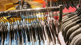 Stylish clothes hanging in row on hangers in a clothing store in a mall. Stylish clothes hanging in a row on hangers in a clothing store in a mall stock video