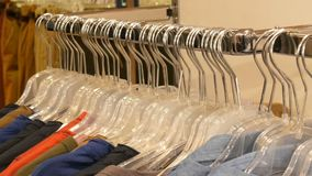 Stylish clothes hanging in row on hangers in a clothing store in a mall. Stylish clothes hanging in a row on hangers in a clothing store in a mall stock footage