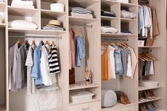 Stylish clothes, shoes and home stuff in large wardrobe. Closet stock photo