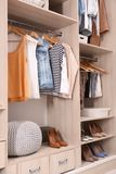 Stylish clothes and shoes in large wardrobe. Closet stock images