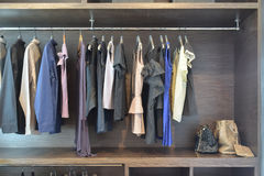 Stylish cloths in dark shade hanging in open wooden wardrobe royalty free stock photography