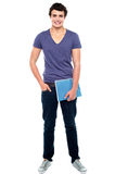 Stylish college student posing with notebook. In one hand and other hand in  pocket Royalty Free Stock Images