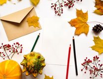Stylish composition of letter, pumpkins, autumn leaves, berries. Top view on white background. Autumn flat lay Royalty Free Stock Images