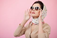Stylish confident brunette woman touching his sunglasses, wearing in scarves, looking up, isolated on a pink background. stock photography