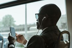 Stylish confident businessman in earphones using smartphone while. Taking train royalty free stock image