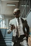Stylish confident businessman using smartphone while walking. On stairs stock photos