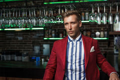 Stylish confident man in suit. Young handsome man in striped shirt and red jacket posing confidently on background of bar Stock Photography