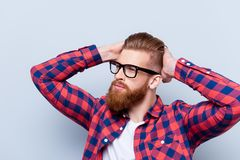 Stylish confident young bearded man in checkered shirt and glass. Es touching his haircut against gray background Stock Photography