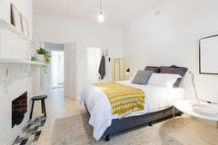 Stylish contemporary bedroom with ensuite and yellow accents Royalty Free Stock Photos