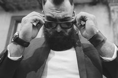 Stylish cool bearded man takes off his glasses Stock Images