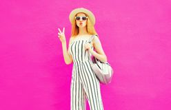 stylish cool girl in summer round straw hat, white striped jumpsuit with backpack on colorful pink wall stock photo