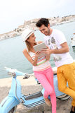 Stylish couple with blue scooter using tablet Stock Photography