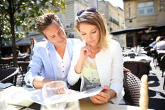 Stylish couple choosing menu in outdoor restaurant Royalty Free Stock Photography