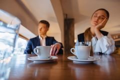 A stylish couple drinks morning coffee at the cafe, the girl is sleeping, the boy is looking out the window royalty free stock photos