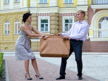 Stylish couple fighting over luggage Stock Photos