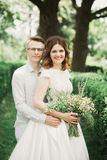 Stylish couple of happy newlyweds walking in the park on their wedding day with bouquet Stock Photography