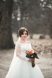 Stylish couple of happy stylish newlyweds walking in the  park on their wedding day with bouquet Stock Image