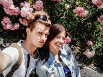 Stylish couple hipsters traveling in europe city and having self. Ie on background of sunny roses royalty free stock image