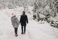 Free Stylish Couple Holding Hands And Walking In Winter Snowy Mountai Royalty Free Stock Images - 129663279