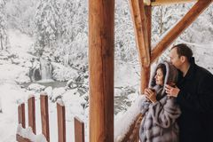 Stylish couple holding hot tea in cups and looking at winter snowy mountains from wooden porch. Happy romantic family with drinks royalty free stock photos